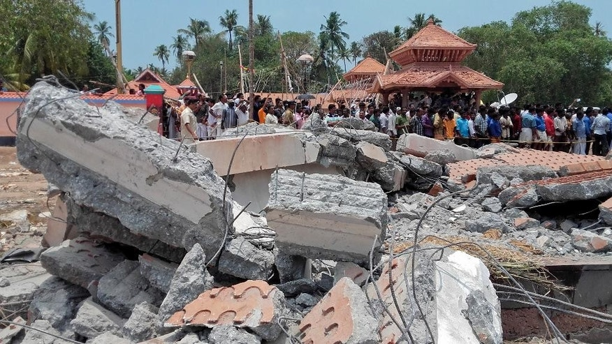A view of a collapsed building after a massive fire broke out during a fireworks display at the Puttingal temple complex in Paravoor village, north of Thiruvananthapuram, southern Kerala state, India, Sunday, April 10, 2016. Dozens were killed and many more were injured when a spark from an unauthorized fireworks show ignited a separate batch of fireworks that were being stored at the temple complex, officials said. Most of the people died when the building where the fireworks were stored collapsed, said Chief Minister Oommen Chandy, the state's top elected official.(Photo via AP)