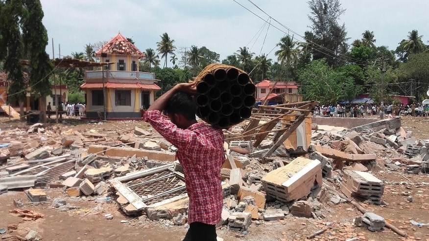 A man walks carrying empty shells of fireworks past a collapsed building after a massive fire broke out during a fireworks display at the Puttingal temple complex in Paravoor village, north of Thiruvananthapuram, southern Kerala state, India, Sunday, April 10, 2016. Dozens were killed and many more were injured when a spark from an unauthorized fireworks show ignited a separate batch of fireworks that were being stored at the temple complex, officials said. Most of the people died when the building where the fireworks were stored collapsed, said Chief Minister Oommen Chandy, the state's top elected official.(Photo via AP)