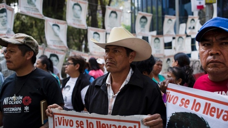 "Relatives of 43 missing students from the Isidro Burgos rural teachers' college hold pictures of their missing loved ones after meeting with  Attorney General Arely Gomez Gonzalez in Mexico City, Thursday, March 17, 2016. His sign reads in Spanish: ""They took them alive!."" In September of 2014, several students and bystanders were killed and 43 students vanished in the city of Iguala, allegedly taken by police and then handed over to a criminal gang who burned their bodies in a garbage dump, according to a federal investigation. Families of the missing and independent investigators cast doubts on the official version. (AP Photo/Eduardo Verdugo)"