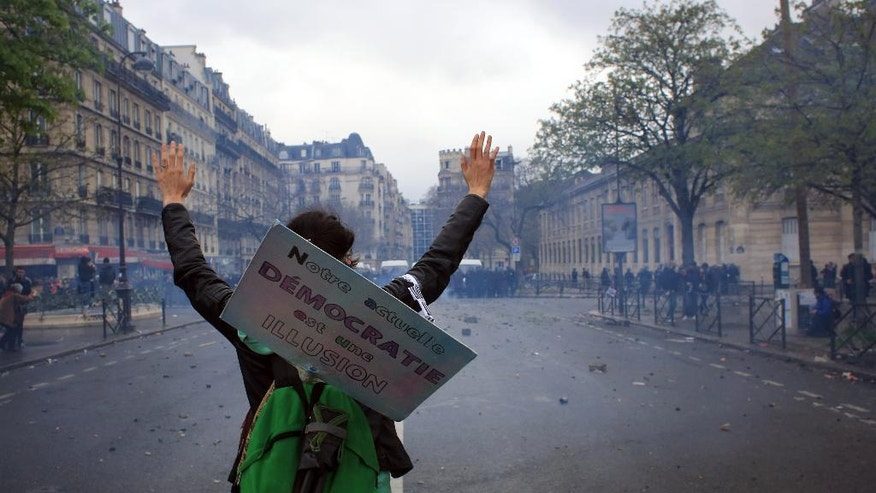 "A demonstrators attends a protest against proposed changes to France's work week and layoff practices, in Paris, Saturday, April 9, 2016. Protesters across France are marching to voice their anger at labor reforms being championed by the country's Socialist government. The board reads: "" Our democracy is an illusion"". (AP Photo/Thibault Camus)"