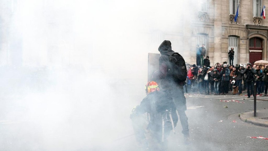 Demonstrators clash with riot police during clashes against police officers, as part of a protest against the proposed changes to France's working week and layoff practices, in Paris, Saturday, April 9, 2016. Protesters across France are marching to voice their anger at labor reforms being championed by the country's Socialist government. (AP Photo/Thibault Camus)