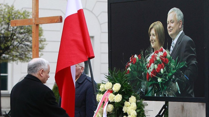Poland's ruling party leader, Jaroslaw Kaczynski, lays a wreath  in front of  the portrait of his late twin brother,  the former President Lech Kaczynski, and  his wife Maria Kaczynska, at the Presidential Palace in Warsaw, Poland, on Sunday, April  10, 2016, during ceremonies marking six years since the presidential couple and dozens of other state officials were killed in a plane crash in Russia. (AP Photo/Czarek Sokolowski)