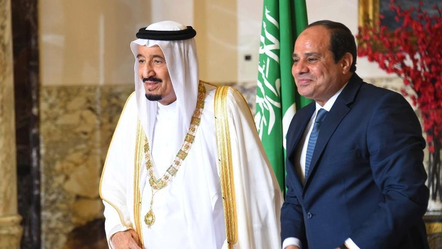 In this picture taken Friday, April 8, 2016, provided by the office of the Egyptian Presidency, Egyptian President Abdel-Fattah el-Sissi, right, standas with Saudi Arabia's King Salman in Cairo.  Egypt welcomed Saudi Arabia's monarch on a landmark visit to the Arab world's most populous country on Thursday, with Cairo seeking to boost ties and garner deals to prop up the nation's shaky economy despite some persistent divisions with the Sunni powerhouse. (Mohamed Abd El Moatey, Egyptian Presidency via AP)
