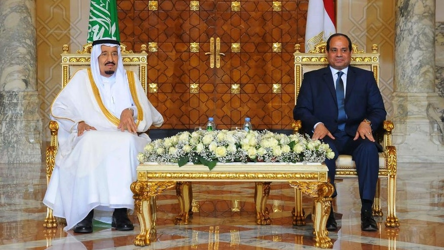 In this picture taken Friday, April 8, 2016, provided by the office of the Egyptian Presidency, Egyptian President Abdel-Fattah el-Sissi, right, sits with Saudi Arabia's King Salman in Cairo.  Egypt welcomed Saudi Arabia's monarch on a landmark visit to the Arab world's most populous country on Thursday, with Cairo seeking to boost ties and garner deals to prop up the nation's shaky economy despite some persistent divisions with the Sunni powerhouse. (Fady Faris, Egyptian Presidency via AP)