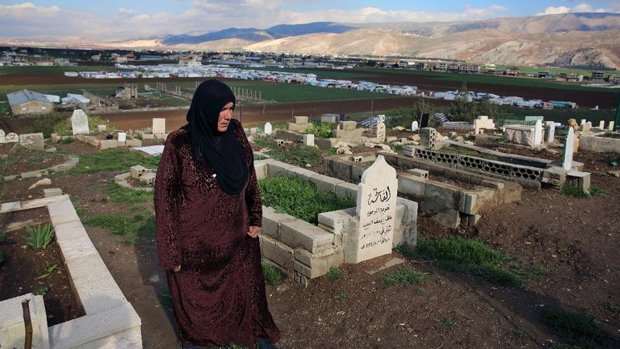In this Tuesday, March 29, 2016 photo, Syrian refugee Saada Khalaf, 45, who fled from the city of Homs, Syria, walks in the cemetery in the eastern village of Dalhamyeh, in the Bekaa valley, Lebanon. With many cemeteries almost full, Syrians are facing difficulties finding places where they can bury their loved ones who die in Lebanon. Most are not able to take them back for burial in Syria because of the dangers and closed roads _ just some of the results of the five-year civil war that has killed more than a quarter million people and displaced half the country's pre-war population. (AP Photo/Bilal Hussein)