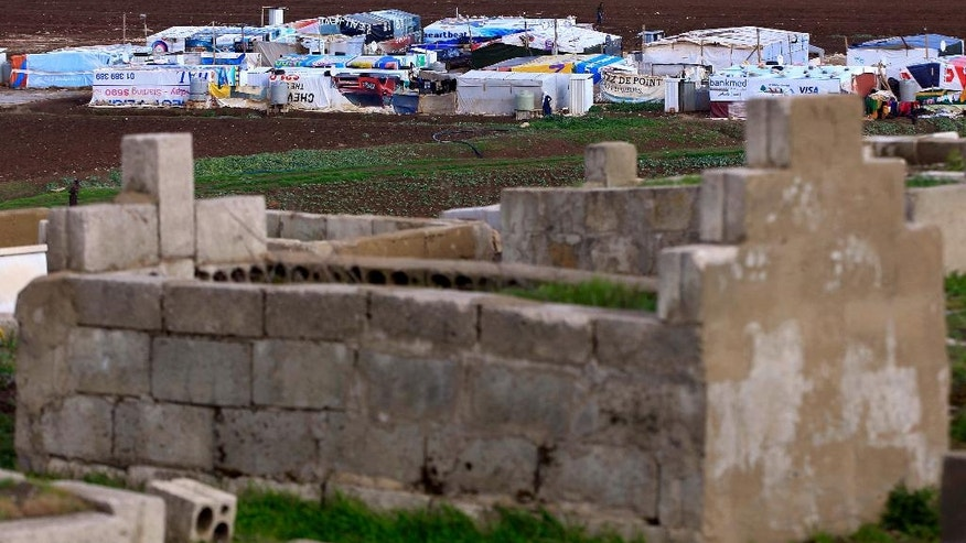 In this Tuesday, March 29, 2016 photo, a Syrian refugee camp is seen from the cemetery of the eastern village of Dalhamyeh, in the Bekaa valley, Lebanon. With many cemeteries almost full, Syrians are facing difficulties finding places where they can bury their loved ones who die in Lebanon. Most are not able to take them back for burial in Syria because of the dangers and closed roads _ just some of the results of the five-year civil war that has killed more than a quarter million people and displaced half the country's pre-war population. (AP Photo/Bilal Hussein)