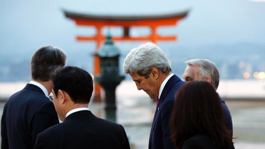 U.S. Secretary of State John Kerry, second right, and France's Foreign Minister Jean-Marc Ayrault, right, walk with Japan's Foreign Minister Fumio Kishida, second left, as they visit the Itsukushima Shrine during a cultural break in Miyajima Island from their G7 foreign ministers meetings in nearby Hiroshima, Japan, Sunday, April 10, 2016. (Jonathan Ernst/Pool Photo via AP)