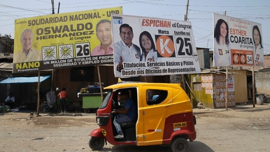 Billboards promote presidential candidate Keiko Fujimori, center right, and congressional candidate Oswaldo Hernandez, left, in a shantytown in Lima, Peru, Saturday, April 9, 2016. Polls show Keiko Fujimori as the favorite going into Sunday's presidential contest, with a double-digit lead, although she is expected to fall short of capturing the simple majority of votes needed to avoid a June runoff. (AP Photo/Martin Mejia)