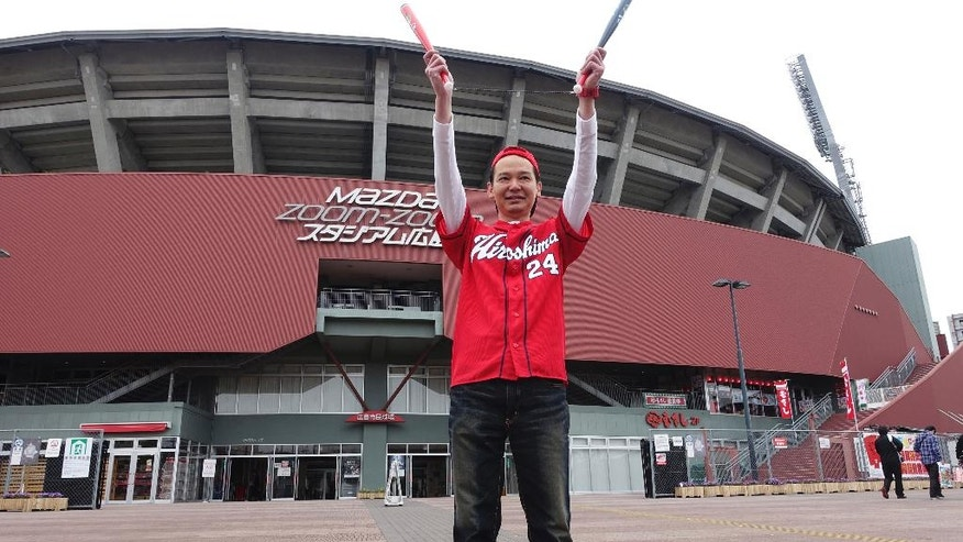 In this Sunday April 10, 2016 photo, Hiroyuki Yokoyama, a 46-year-old supporter of Hiroki Yokoyama, a right-hander for the Hiroshima Toyo Carp, poses for a photo in front of the team's home stadium as he wished a victory for the team's away game later, in Hiroshima, western Japan. This year's two-day Group of Seven foreign ministers' meeting started Sunday. (AP Photo/Mari Yamaguchi)