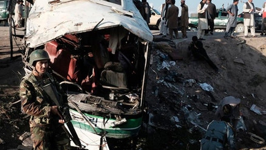 Afghans inspect damages of a bus after a suicide attack in Jalalabad east of Kabul, Afghanistan, Monday, April 11, 2016. An Afghan official says that at least 12 new army recruits have been killed in a suicide bomb attack in the eastern city of Jalalabad. (AP Photo/Mohammad Anwar Danishyar)