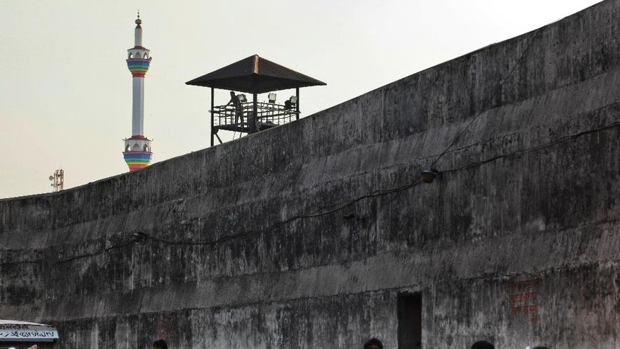 In this April 10, 2016 photo, a prison guard looks over a busy street adjoining the Dhaka Central Jail in Dhaka, Bangladesh. The government is closing its notorious 18th-century prison where sensational political killings over decades have targeted people on both sides of the South Asian country's 1971 war for independence from Pakistan. (AP Photo/ A.M. Ahad)