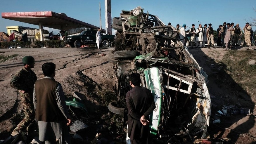 Afghans inspect the damages of a bus after a suicide attack in Jalalabad east of Kabul, Afghanistan, Monday, April 11, 2016. An Afghan official says that at least 12 new army recruits have been killed in a suicide bomb attack in the eastern city of Jalalabad. (AP Photo/Mohammad Anwar Danishyar)