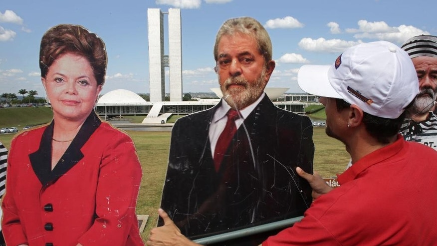 A demonstrator puts up cut out photos depicting Brazil's President Dilma Rousseff, left, and former President Luiz Inacio Lula da Silva during protest in favor of Rousseff's impeachment, in front of the National Congress, in Brasilia, Brazil , Monday, April 11, 2016.  Efforts to remove President Rousseff are advancing as a congressional commission meets to decide whether it should recommend impeachment to the full lower house of Congress. (AP Photo/Eraldo Peres)
