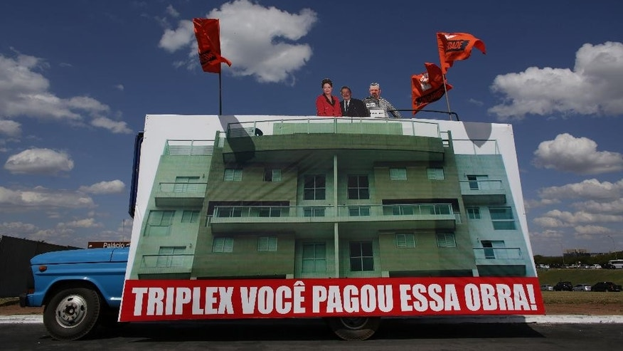 "A truck carries large sign with cut out images depicting Brazil's President Dilma Rousseff, Former President Luiz Inacio Lula da Silva, and Workers Party treasurer Delubio Soares, on the roof of a triplex apartment located in Guaruja beach and property of Lula da Silva, during protest in favor of impeachment of Brazil's President Dilma Rousseff, in front of the National Congress, in Brasilia, Brazil , Monday, April 11, 2016.  The sign reads in Portuguese ""This triplex payed by you!"" Efforts to remove Brazilian President Dilma Rousseff are advancing as a congressional commission meets to decide whether it should recommend impeachment to the full lower house of Congress. (AP Photo/Eraldo Peres)"