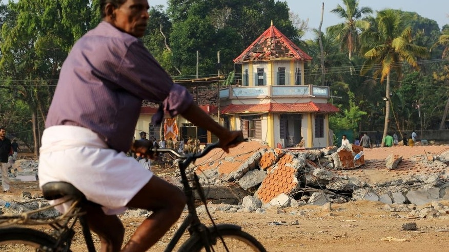 A cyclist rides past damaged structures at the spot where a massive fire broke out during a fireworks display at the Puttingal temple complex in Paravoor village, Kollam district, southern Kerala state, India, Monday, April 11, 2016. Rescue officials on Monday sifted through a Hindu temple in southern India where at least 110 people died when a fireworks display - an unauthorized pyrotechnic display that went horribly wrong - swept through a temple packed with thousands for a religious festival. (AP Photo/Aijaz Rahi)