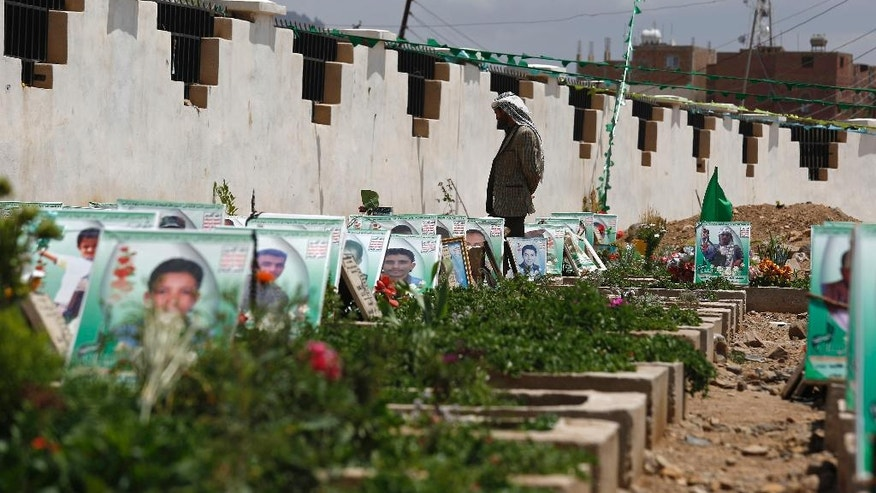A Shiite rebel Houthi stands among the portrait adorned graves of  Houthi fighters and supporters who were killed in the ongoing conflict in Yemen, a few hours before the start of a fresh cease-fire, in Sanaa, Yemen, Sunday, April 10, 2016. (AP Photo/Hani Mohammed)