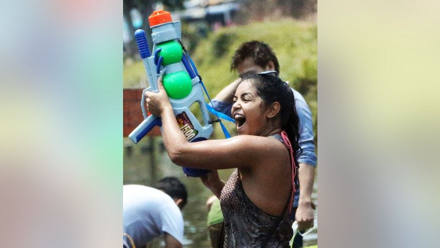 FILE - In this April 13, 2014 file photo, a foreign tourist holds a water gun as she takes part in a water fight during traditional Thai New Year celebrations or Songkran festival in Chiang Mai province, northern Thailand. Thailand's military government is putting a dampener on the annual nationwide water fight. Despite Thailand's worst drought in 20 years, the junta says it has no intention of limiting the virtually around-the-clock water throwing that defines the three-day Songkran festival. Instead, it has decided to impose morality measures.(AP Photo/Apichart Weerawong, File)