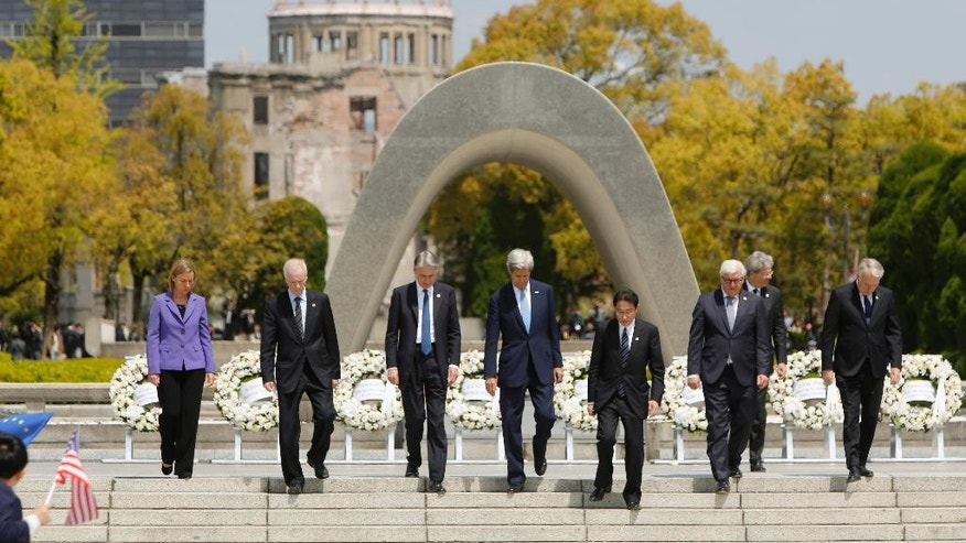 G7 foreign ministers, from left to right, E.U. High Representative for Foreign Affairs Federica Mogherini, Canada's Foreign Minister Stephane Dion, Britain's Foreign Minister Philip Hammond, U.S. Secretary of State John Kerry, Japan's Foreign Minister Fumio Kishida, Germany's Foreign Minister Frank-Walter Steinmeier, Italy's Foreign Minister Paolo Gentiloni and France's Foreign Minister Jean-Marc Ayrault walk together after placing wreaths at the cenotaph at Hiroshima Peace Memorial Park  in Hiroshima, western Japan, Monday, April 11, 2016. (Jonathan Ernst/Pool Photo via AP)