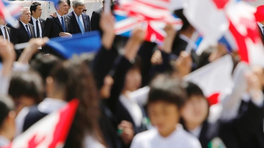 School children hold national flags as France's Foreign Minister Jean-Marc Ayrault, left, Britain's Foreign Minister Philip Hammond, third left, U.S. Secretary of State John Kerry, fourth left, and other G7 foreign ministers visit Hiroshima Peace Memorial Park in Hiroshima, western Japan, Monday, April 11, 2016. (Jonathan Ernst/Pool Photo via AP)