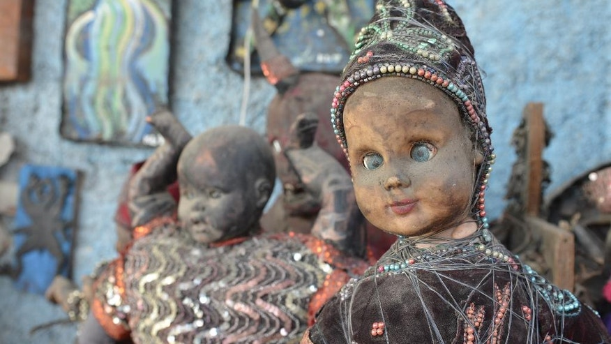 In this April 2, 2016 photo, dusty sculptures made of cast-off baby dolls sit in an open-air museum and art workshop off a trash-strewn street cutting through some of the poorest neighborhoods in Port-au-Prince, Haiti. They were created by Haitian artists called Atis Rezistans who have become celebrated in the international art world by creating sculptures out of scrapped car parts, old wood, discarded toys and even human skulls found scattered outside crumbling mausoleums. (AP Photo/David McFadden)