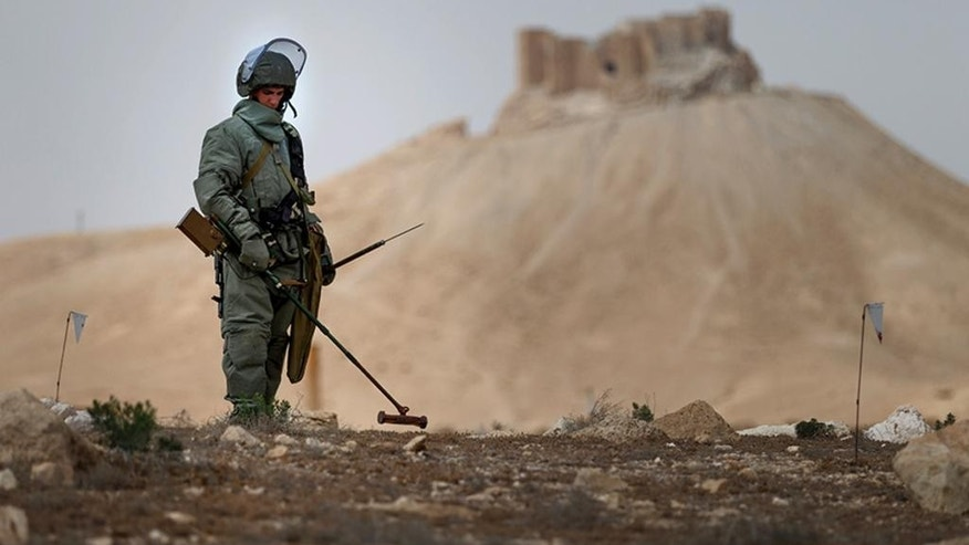 In this photo taken Friday, April 8, 2016 and  provided by Russian Defense Ministry press service, a Russian serviceman checks for mines in Palmyra, Syria. Russian combat engineers arrived in Syria on a mission to clear mines in the ancient town of Palmyra, which has been recaptured from Islamic State militants in an offensive that has proven Russia's military might in Syria despite a drawdown of its warplanes. (Russian Defense Ministry Press Service Photo via AP)