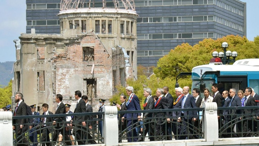 U.S. Secretary of State John Kerry, center, walks past A-Bomb Dome after visiting the site in Hiroshima, western Japan Monday, April 11, 2016. Kerry visited the revered memorial to Hiroshima's atomic bombing on Monday, delivering a message of peace and hope for a nuclear-free world seven decades after United States used the weapon for the first time in history and killed 140,000 Japanese. (Shingo Nishizume/Kyodo News via AP) JAPAN OUT, MANDATORY CREDIT