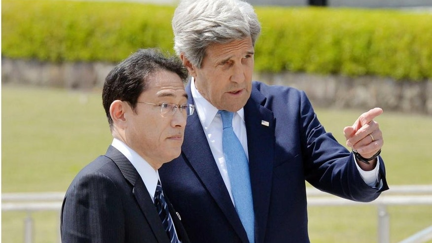 Japan's Foreign Minister Fumio Kishida, left, and U.S. Secretary of State John Kerry talk after offering wreaths at the cenotaph at Hiroshima Peace Memorial Park in Hiroshima, western Japan Monday, April 11, 2016. Kerry visited the revered memorial to Hiroshima's atomic bombing on Monday, delivering a message of peace and hope for a nuclear-free world seven decades after United States used the weapon for the first time in history and killed 140,000 Japanese. (Kyodo News via AP) JAPAN OUT, MANDATORY CREDIT