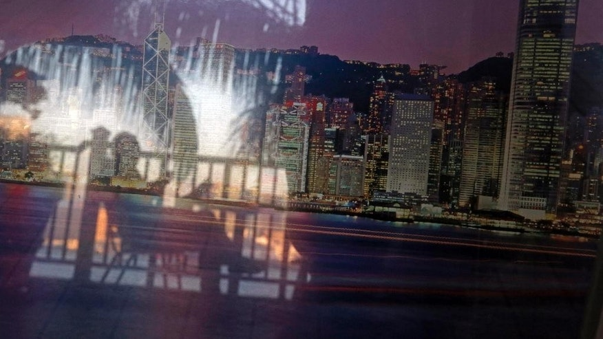 In this March 2, 2016 photo, a man is reflected on the glass display with an image of the night skyline in Hong Kong. Hong Kong has emerged as a major design center for offshore vehicles, a place brimming with people expert at packaging and protecting wealth. The back pages of newspapers here teem with advertisements for corporate formation companies, one-stop shops promising fast bank account opening, corporate compliance, tax and accountancy services. Offshore vehicles are used to minimize tax, mitigate political risk, and circumvent onerous regulations in China. And they are completely legal. (AP Photo/Kin Cheung)