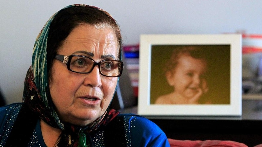 FILE - In this Thursday, April 7, 2016 file photo, Lebanese Ibtissam Berri speaks during an interview with The Associated Press as she sits next to a picture of her granddaughter Lahela al-Amin, at her home in the southern suburbs of Beirut, Lebanon. A state prosecutor in Lebanon is expected to file kidnapping charges against an Australian woman, an Australian TV crew, and others Monday for attempting to take the woman's two children away from their paternal grandmother and spirit them back to Australia.  (AP Photo/Bilal Hussein, File)