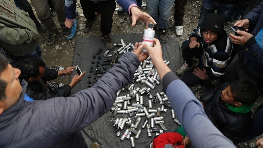 Migrant men display used tear gas canisters apparently used by Macedonian police during yesterday riots at the fence in the makeshift camp of the northern Greek border point of Idomeni, Greece, Monday, April 11, 2016. More than 12,000 people have been stuck at the Idomeni border point for more than a month hoping that it would reopen. (AP Photo/Amel Emric)