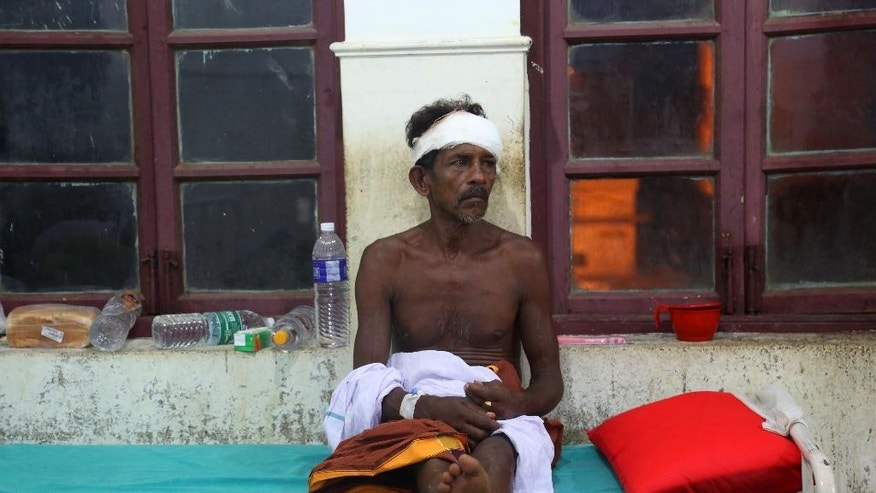 An injured man rests on a bed at the Kollam district hospital after a massive fire broke out during a fireworks display at the Puttingal temple complex in Paravoor village, Kollam district, southern Kerala state, India, Sunday, April 10, 2016. Dozens were killed and many more were injured when a spark from an unauthorized fireworks show ignited a separate batch of fireworks that were being stored at the temple complex, officials said. (AP Photo/Aijaz Rahi)