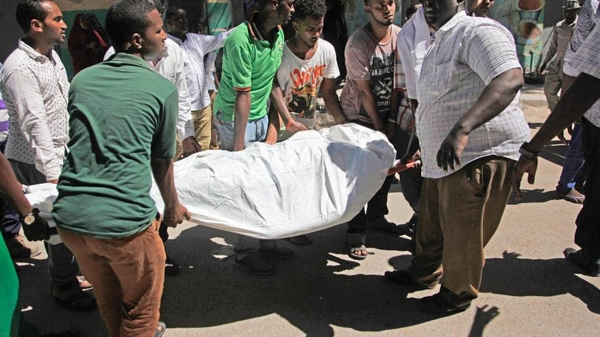 Somalis carry away a dead body from the scene of a car bomb attack in the capital Mogadishu, Somalia, Monday, April 11, 2016. A car bomb exploded outside a restaurant packed with lunchtime customers, killing at least five people according to witnesses in the capital's Hamarweyne district, close to the municipal government headquarters and a busy commercial area. (AP Photo/Farah Abdi Warsameh)