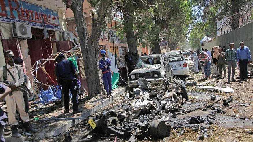 Security forces and others inspect the scene of a car bomb attack in the capital Mogadishu, Somalia, Monday, April 11, 2016. A car bomb exploded on Monday outside restaurant packed with lunchtime customers in the Somali capital of Mogadishu killing at least five people, said witnesses. (AP Photo/Farah Abdi Warsameh)