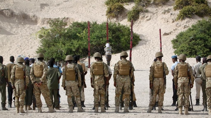 Hassan Hanafi Haji, center, a former journalist accused of belonging to al-Shabab and involvement in the killings of five Somali journalists, is tied to a wooden post as he is prepared to be executed by firing squad, at a police academy in the capital Mogadishu, Somalia Monday, April 11, 2016. Haji, who was extradited from Kenya last year on the request of the Somali government, was executed by firing squad which remains the only execution method in Somalia. (AP Photo/Farah Abdi Warsameh)