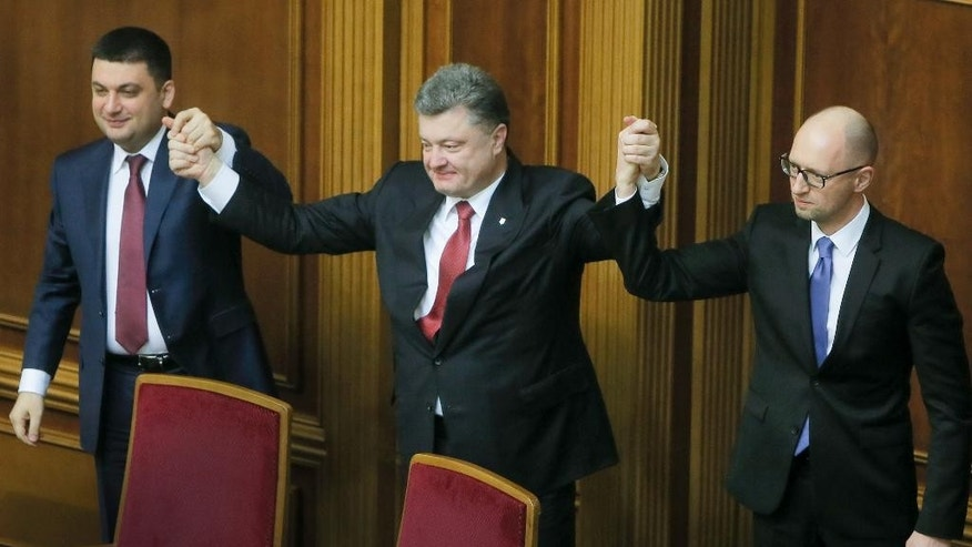 FILE In this Thursday, Nov. 27, 2014 file photo Ukraine's President  Petro Poroshenko, center,  Prime Minister Arseniy Yatsenyuk, right, and parliament speaker  Volodymyr  Groysman celebrate after Yatsenyuk was appointed the Prime Minister during the opening first session of the Ukrainian parliament in Kiev, Ukraine. Prime Minister Arseniy Yatsenyuk, one of the leaders of the Maidan protests, announced Sunday that he would submit his resignation to parliament on Tuesday. This cleared the way for the parliament speaker, Volodymyr Groysman, to replace him and form a new government. The parties led by Yatsenyuk and President Petro Poroshenko will still dominate the governing coalition, but the choice of Groysman, a member of Poroshenko's party, was seen as strengthening the hand of the president. (AP Photo/Efrem Lukatsky, file)