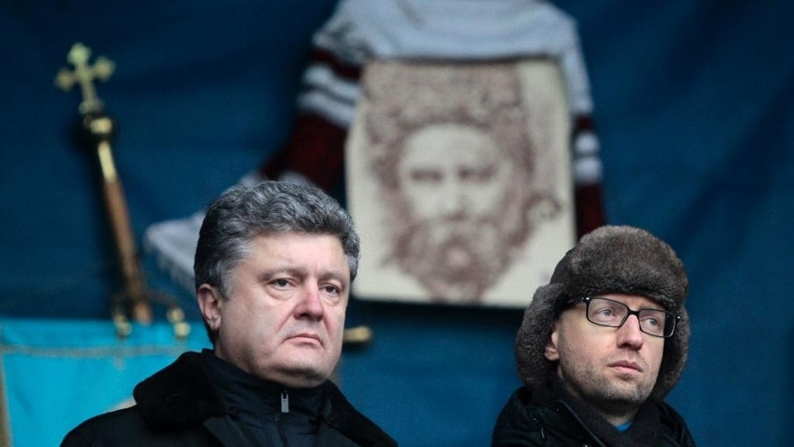 FILE -  In this Sunday, Feb. 9, 2014 file photo then Ukrainian lawmaker and opposition leader Petro Poroshenko, left, and then Ukrainian opposition leader Arseniy Yatsenyuk  attend a rally in the Independence Square in Kiev, Ukraine.  Prime Minister Arseniy Yatsenyuk, one of the leaders of the Maidan protests, announced Sunday that he would submit his resignation to parliament on Tuesday. This cleared the way for the parliament speaker, Volodymyr Groysman, to replace him and form a new government. The parties led by Yatsenyuk and President Petro Poroshenko will still dominate the governing coalition, but the choice of Groysman, a member of Poroshenko's party, was seen as strengthening the hand of the president. (AP Photo/Sergei Chuzavkov, file)