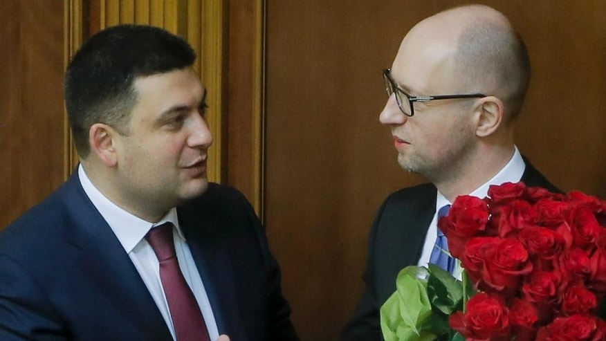 FILE- - In this Thursday, Nov. 27, 2014 Prime Minister Arseniy Yatsenyuk, right, and parliament speaker Volodymyr Groysman celebrate after Yatsenyuk was appointed the Prime Minister during the opening first session of the Ukrainian parliament in Kiev, Ukraine. Prime Minister Arseniy Yatsenyuk, one of the leaders of the Maidan protests, announced Sunday April 10, 2016  that he would submit his resignation to parliament on Tuesday. This cleared the way for the parliament speaker, Volodymyr Groysman, to replace him and form a new government. The parties led by Yatsenyuk and President Petro Poroshenko will still dominate the governing coalition, but the choice of Groysman, a member of Poroshenko's party, was seen as strengthening the hand of the president. (AP Photo/Efrem Lukatsky, file)