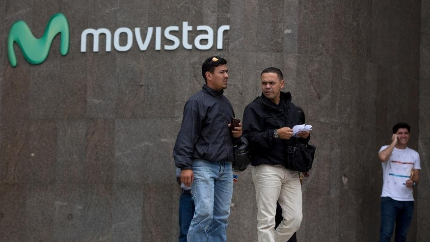 Pedestrians walk outside Movistar a cell phone company office in the Chacao municipality of Caracas, Venezuela, Monday, April 11, 2016. Movistar, a subsidiary of the Spanish-based Telefonica, and Digitel both announced last week that they would be cutting international service because of issues related to Venezuela's byzantine currency controls. (AP Photo/Fernando Llano)