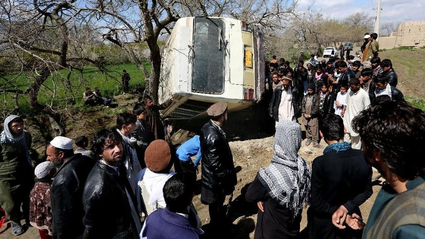 Afghans gather at the site of a roadside bomb explosion on the outskirts of Kabul, Afghanistan, Monday, April 11, 2016. An Afghan official says at least one person has been killed when a bomb ripped through a bus carrying education ministry employees to work in the capital, Kabul. (AP Photo/Rahmat Gul)