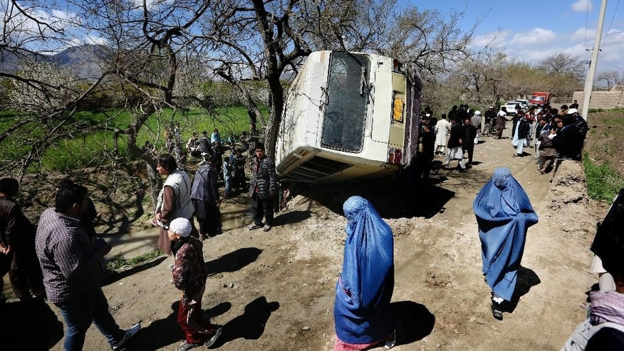 In this Monday, April 11, 2016. file, photo, Afghan women walk past a damaged bus after a roadside bomb explosion on the outskirts of Kabul, Afghanistan, The Afghan Taliban have announced the start of their warm-weather fighting season, an annual declaration that marks the launch of a summer of violence. (AP Photo/Rahmat Gul)