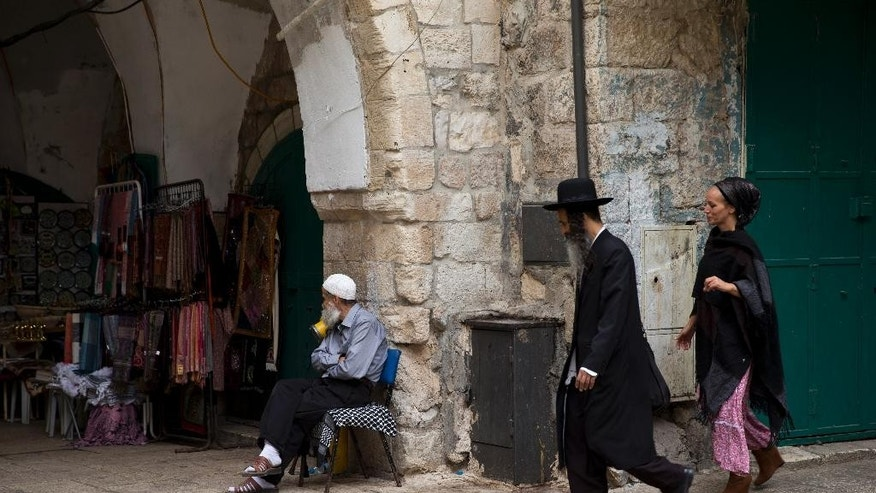 FILE - In this Friday, Oct. 9, 2015 file photo, a Jewish couple walk past a Palestinian man in the old city in Jerusalem. After a months-long surge in Israeli-Palestinian violence, Jerusalem is struggling to return to its routine as Palestinian attacks have subsided. But beneath the veneer of normalcy, the city is struggling to conceal the scars and some worry about the possibility of renewed violence as the popular spring holiday season kicks into gear. (AP Photo/Ariel Schalit, File)