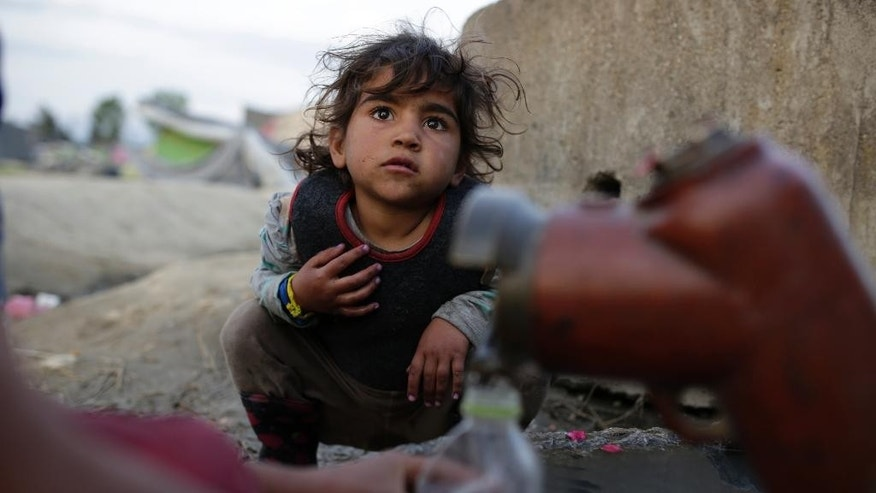 Migrant girls waits on public water pipe to fill water, at the makeshift camp at the northern Greek border point of Idomeni, Greece, Monday, April 11, 2016. More than 12,000 people have been stuck her for more than a month amid hopes that the border would reopen. (AP Photo/Amel Emric)