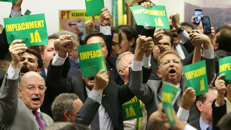 "April 11, 2016: As they hold a sign reading ""impeachment now"" opposition lawmakers celebrate after the results of the voting at a congressional committee in Brasilia, Brazil"