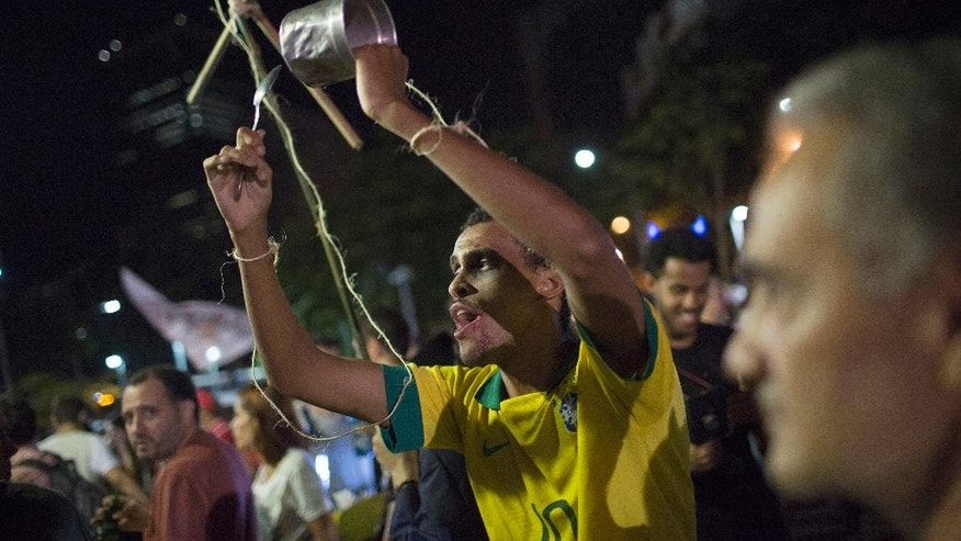 A supporter of President Dilma Rousseff acts like a puppet being manipulated by another person during a demonstration against Rousseff's impeachment process, in Rio de Janeiro, Brazil, Monday, April 11, 2016. As a congressional committee voted Monday to recommend that the process to impeach Rousseff move forward thousands of her supporters turned out for anti-impeachment events in downtown Rio de Janeiro, attended by top musicians, artists and former President Luiz Inacio Lula da Silva.  (AP Photo/Leo Correa)