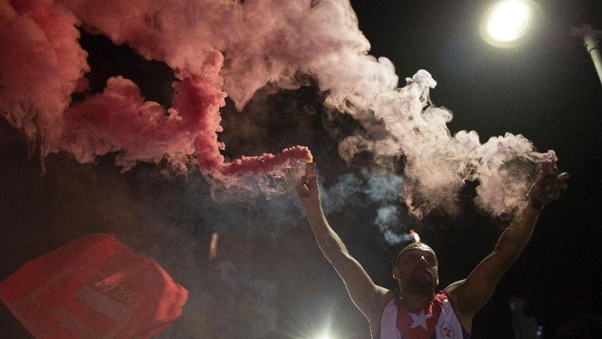 A supporter holds flares during a demonstration in support of Brazil's President Dilma Rousseff and against her impeachment process, in Rio de Janeiro, Brazil, Monday, April 11, 2016. Rousseff is accused of manipulating budget accounts to allow her administration to boost spending to shore up votes ahead of her 2014 re-election campaign and she calls the impeachment effort an attempted coup. (AP Photo/Leo Correa)