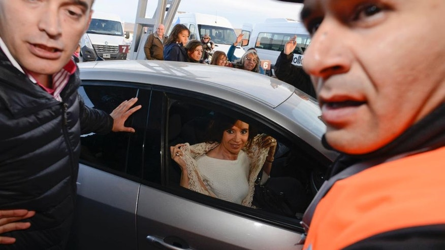 Former Argentina's President Cristina Fernandez is surrounded by supporters and security as she arrives to fly out of the airport in El Calafate, Argentina, Monday, April 11, 2016. After spending four months in Patagonia, Fernandez' supporters gave her a hero's welcome at a Buenos Aires airport before she faces a court over her possible role in an alleged scheme to manipulate the country's currency. (AP Photo/Francisco Munoz)