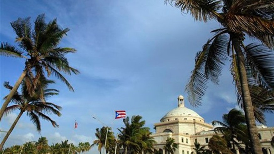 In this July 29, 2015, file photo, U.S. and Puerto Rican flags fly in front of Puerto Ricoâs Capitol as in San Juan, Puerto Rico. As Puerto Rico teeters on the brink of insolvency, the The Roman Catholic Archdiocese of San Juan has told several hundred current and retired teachers that their pensions have been dispensed with because payouts exceeded contributions. The island has no law overseeing private pensions and itâs unclear if the archdioceseâs fund was insured. (AP Photo/Ricardo Arduengo, File)