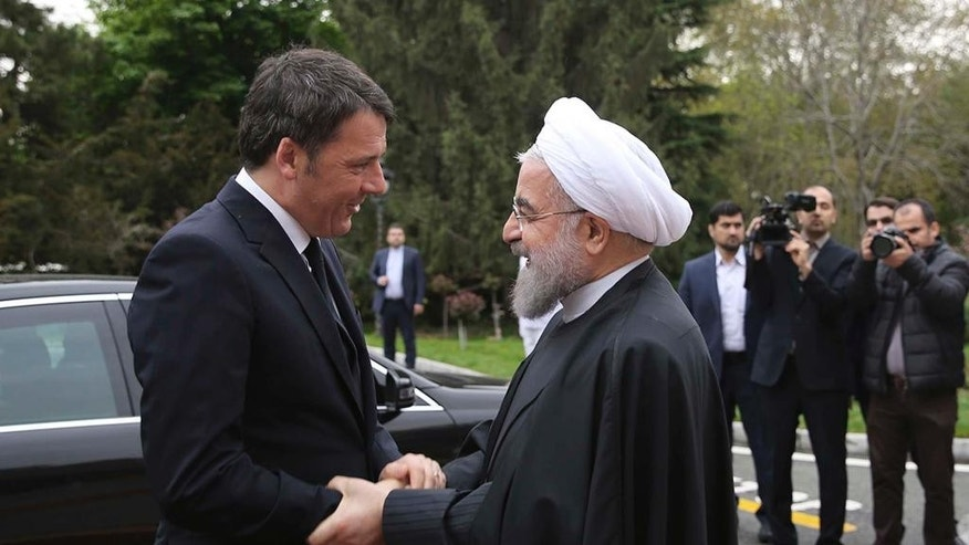 In this photo released by official website of the Iranian Presidency office, Iran's President Hassan Rouhani, right, welcomes Italian Prime Minister Matteo Renzi during an official arrival ceremony at the Saadabad Palace in Tehran, Iran, Tuesday, April 12, 2016. (Iranian Presidency Office via AP)