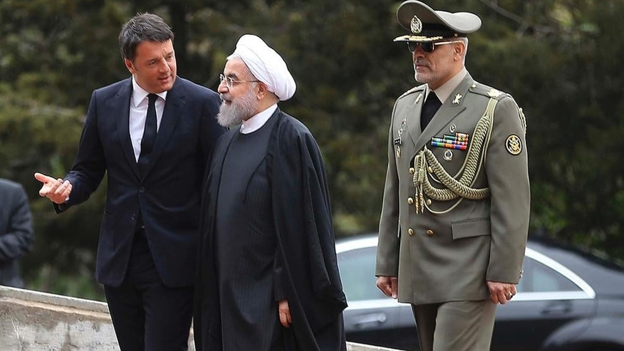 In this photo released by official website of the Iranian Presidency office, Italian Prime Minister Matteo Renzi, left, speaks with Iran's President Hassan Rouhani during his official arrival ceremony at the Saadabad Palace in Tehran, Iran, Tuesday, April 12, 2016. (Iranian Presidency Office via AP)