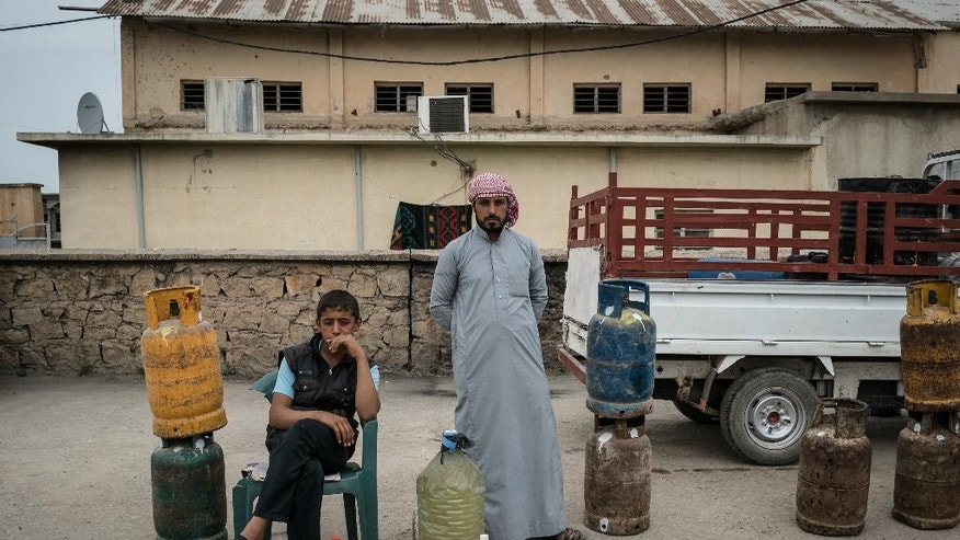 In this April 9, 2016 photo, a man and boy sell gas cylinders in central Rabia, northwestern Iraq. When Iraqi Kurdish forces retook Rabia last year it was a major advance against the Islamic State group, which had swept across northern and western Iraq in the summer of 2014 and declared its caliphate across its territory in Iraq and Syria. Now 18 months later, the town demonstrates the difficulties of returning to the way things were before the IS rampage. (AP Photo/Alice Martins)